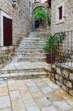 Frau-Tourist steigt Treppe auf Straße in der alten Stadt, Ulcinj, Montenegro ab Lizenzfreies Stockbild