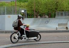 Frau trägt ein Kind in einer Fahrradlaufkatze Lizenzfreie Stockfotos