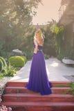 Frau trägt langes purpurrotes Kleid Stockbild