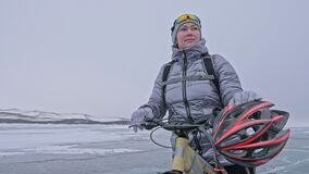 Frau trägt Sportausrüstung Das Mädchen wird in einer silbrigen unten Jacke, in einem Radfahrenrucksack und in einem Sturzhelm gek stock video