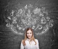 Frau träumt über das Einkaufen Einkaufsikonen werden auf die schwarze Tafel gezeichnet Lizenzfreie Stockbilder