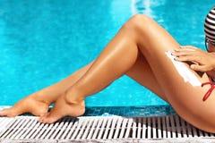 Frau tragen Sonnenschutzcreme auf ihren glatten gebräunten Beinen auf Schöne Beine draußen durch Pool unter Sonnenschein am schön Lizenzfreies Stockfoto
