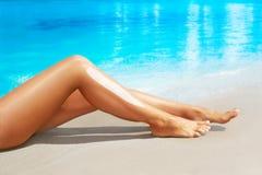Frau tragen Sonnenschutzcreme auf ihren glatten gebräunten Beinen auf sunscreen Stockbilder