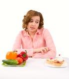 Frau trifft Wahl von den Kuchen und vom Gemüse Lizenzfreies Stockbild
