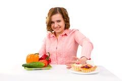 Frau trifft Wahl von den Kuchen und vom Gemüse Stockfoto
