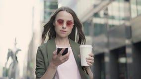 Frau in trinkendem Kaffee der Stadt, in wählender Telefonnummer und im Beginnen zu sprechen stock video