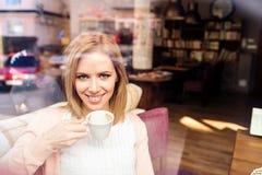Frau in trinkendem Kaffee des Cafés, Straßenreflexion im Fenster Stockbilder