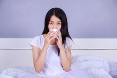 Frau trinkendes acup des Kaffees auf Bett im Schlafzimmer Stockfotografie