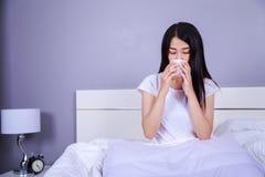 Frau trinkendes acup des Kaffees auf Bett im Schlafzimmer Stockbild
