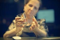 Frau trinkt eine Pille von den Schmerz Stockfotografie
