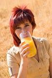 Frau trinkt Glas Saft Stockbild
