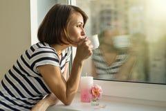 Frau trinkt Kaffee, schaut heraus das Fenster zu Hause Lizenzfreies Stockfoto