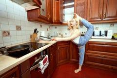 Frau tut Gymnastik in der Küche lizenzfreies stockbild