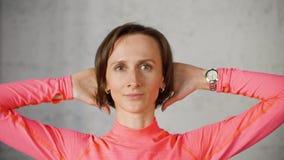 Frau tut Gymnastik mit ihren Händen auf Hals von hinten und Blicken an der Kamera stock video