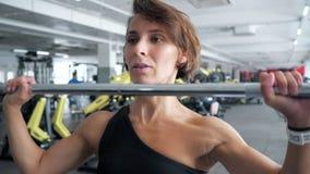 Frau tut Satz Ripse trainieren mit dem Barbell, der ihn über dem Kopf in der Turnhalle anhebt stock footage