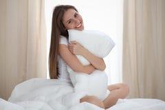 Frau umarmt das Kissen nach aufwachen und erreicht einen Tag glücklich und entspannt nach gutem Nachtschlaf Süße Träume, guter Mo lizenzfreie stockfotos