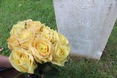 Frau an unbekannter Soldat ` s Grab mit gelben Blumen stockbilder