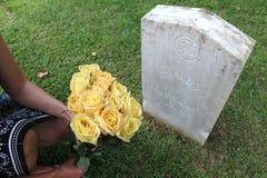 Frau an unbekannter Soldat ` s Grab mit gelben Blumen lizenzfreies stockfoto