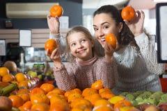 Frau und blondes kleines Mädchen, die whith Mandarine in der Abteilung aufwerfen Lizenzfreies Stockbild