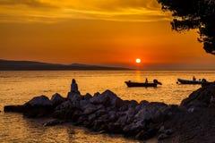 Frau und Boote bei dem Sonnenuntergang Stockbild