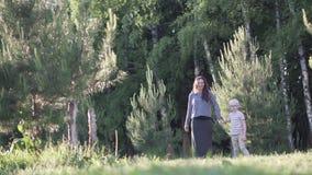 Frau und ein Junge gehen im Wald stock video