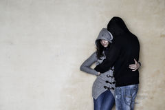 Frau und ein Mann kleideten mit grauer und schwarzer Kleidung, beide tragenden Blue Jeans, das Umarmen an und lehnten sich auf ei Stockfotos