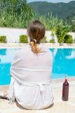 Frau und eine Weinflasche durch das Pool Lizenzfreie Stockbilder