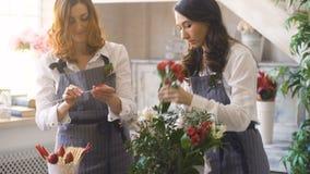 Frau und Florist mit zwei Chefs, die Blumen, Obst und Gemüse für die Herstellung des Fruchtblumenstraußes vorbereiten stock video
