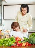 Frau und hübscher Ehemann, die zusammen kochen Stockfotografie