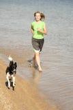 Frau und Hund, die in Wasser laufen Stockbild