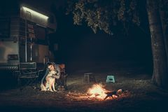 Frau und Hund nahe Lagerfeuer Stockfoto