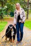 Frau und Hund am Zurückholen des Stockspiels Stockbild
