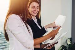 Frau und ihr Assistent, welche die Dokumente besprechen Unternehmensplan und Strategie am Arbeitsplatz verwahrt stockbilder