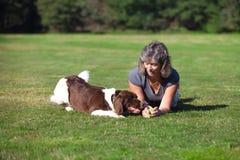 Frau und ihr Hund, die auf dem Gebiet spielen Stockfoto