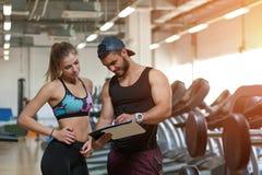Frau und ihr persönlicher Trainer mit Trainingsplan stockbild