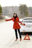 Frau und ihr schädigendes Auto auf der Straße Stockbild