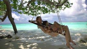 Frau und ihre kleine Tochter genießen einen Rest in einer Hängematte auf dem tropischen Strand stock video footage