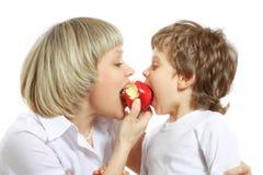 Frau und Junge, die Apfel essen Lizenzfreies Stockfoto