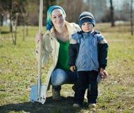 Frau und Junge mit Spaten im Park Stockfotografie