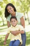 Frau und junger Junge, die draußen umfassen und lächeln Lizenzfreie Stockfotografie