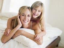 Frau und junges Mädchen, die beim Bettlächeln liegen Lizenzfreie Stockbilder