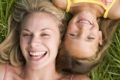 Frau und junges Mädchen, die beim Graslachen liegen Lizenzfreies Stockfoto