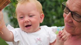 Frau und Kind Älter und jünger Schöne Damen Kleinkind, das mit Fan auf Großmutterhänden spielt