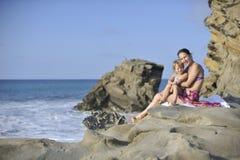 Frau und Kind auf dem felsigen Strand Lizenzfreies Stockfoto
