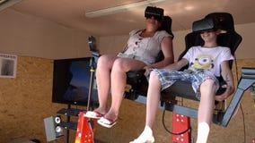 Frau und Kind auf der virtuellen Realität reiten mit Kopfhörer des Gangs VR stock video footage