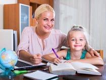 Frau und Kind, die Lektion zuhause haben Stockfoto