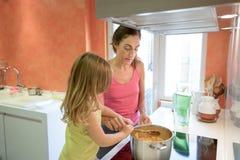 Frau und Kind, die zusammen in der Küche kochen Stockfotografie