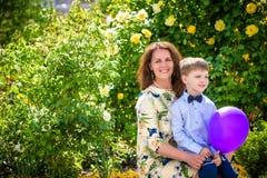 Frau und Kind mit baloon gegen grünen Hintergrund Mutter ` s Tag Mutter und Tochter Lizenzfreie Stockfotografie
