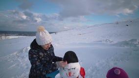 Frau und Kind sculpt zusammen einen Schneemann am H?gel stock footage