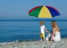 Frau und Kind sitzen unter einem Regenschirm Lizenzfreies Stockfoto